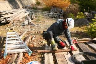 シマフクロウと車両との事故防止のため設置する支柱。一つ一つ針金を固定していきます。